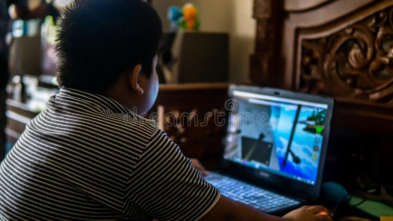 Young kids playing online games on the gaming laptop stock photography