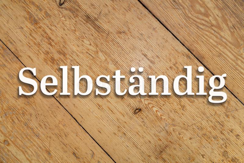 `Selbständig` white text on a wooden background. Translation: `Freelancer`. `Selbständig` white 3D text on a wooden home background. Translation: ` stock photography