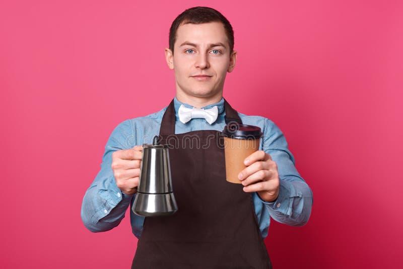 Selbstüberzeugtes hübsches männliches barista hält Kaffeeproduzenten und Wegwerfschale, bereitet Kaffee, vorschlägt, um ihn zu sc lizenzfreies stockbild