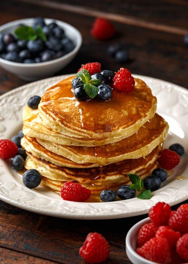 Selbst gemachte amerikanische Pfannkuchen mit frischer Blaubeere, Himbeeren und Honig Rustikale Art des gesunden Morgenfrühstücks stockfoto