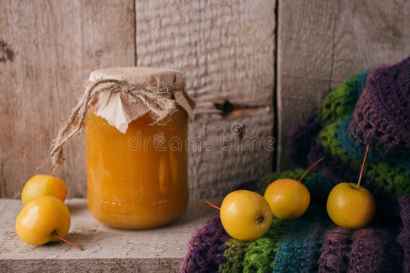 Selbst gemachte Apfelmarmelade in der Bank im Herbsthintergrund mit reifen Äpfeln und Grün verlässt auf dem alten Holztisch, Kopi lizenzfreie stockfotos