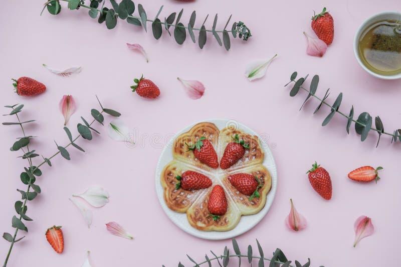 Selbst gemachte belgische Waffeln mit Erdbeeren und Kräutertee auf einem p lizenzfreies stockfoto