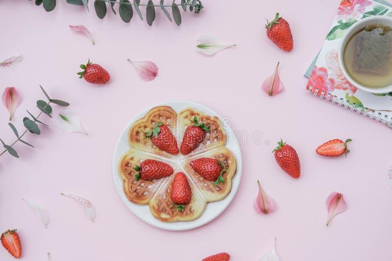 Selbst gemachte belgische Waffeln mit Erdbeeren und Kräutertee auf einem p stockbild