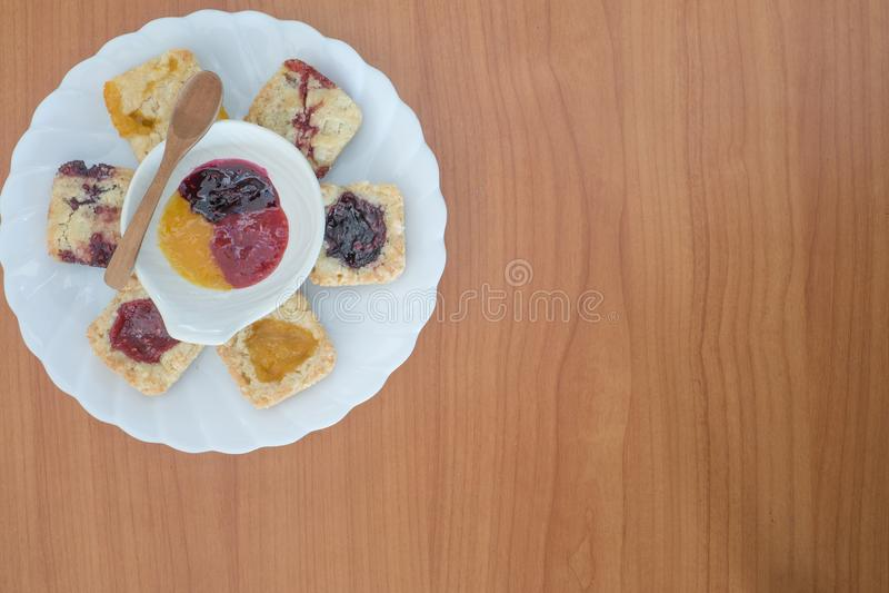 Selbst gemachte Blaubeermarmelade und Orangenmarmelade und Erdbeermarmelade füllten feinschmeckerische Kekskrumenplätzchen stockfoto