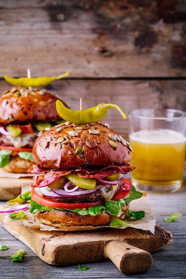 Selbst gemachte Burger mit ganzem Kornbrötchen, gebratenem Speck und würzigen in Essig eingelegten Pfeffern lizenzfreie stockfotografie