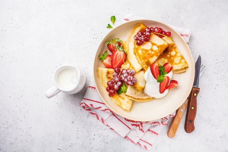 Selbst gemachte dünne Krepps dienten mit Klumpencreme, -korinthen, -erdbeeren und -Puderzucker in der weißen Platte, Draufsicht lizenzfreies stockfoto