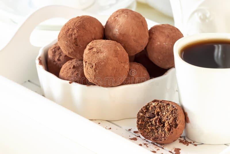 Selbst gemachte dunkle Trüffeln des Schokoladenstrengen vegetariers mit Nussplatten-Lichthintergrund Selektiver Fokus stockfoto