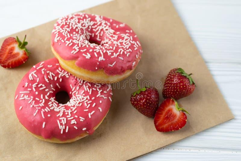 Selbst gemachte frisch gebackene Schaumgummiringe mit dem rosa Erdbeerbereifen stockfotos