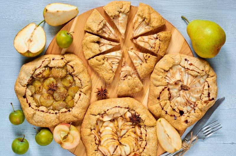 Selbst gemachte Fruchttörtchen mit dem Schokoladenbelag verziert mit Weinlesemesser und -gabel auf dem konkreten Hintergrund lizenzfreie stockfotografie