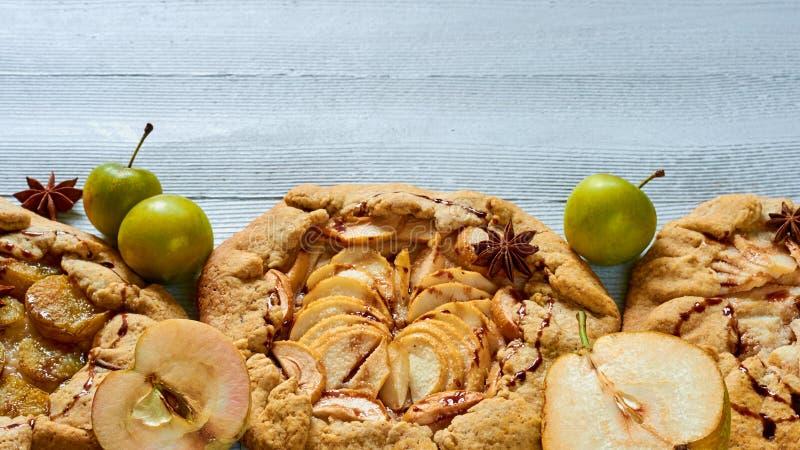 Selbst gemachte Fruchttörtchen mit Schokoladenbelag auf dem konkreten Hintergrund Vegetarischer gesunder Herbstnachtisch - galett stockbilder