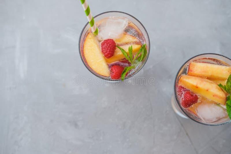 Selbst gemachte gefrorene Limonade oder Tee mit reifen Pfirsichen und Himbeeren lizenzfreies stockfoto