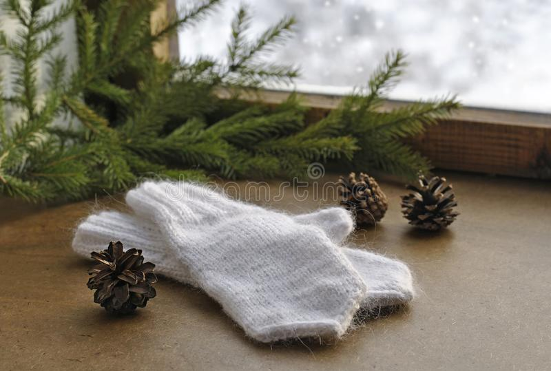 Selbst gemachte gestrickte warme weiße Wollhandschuhe, Tannenzweige und altes hölzernes Winterfenster Weihnachts- oder des neuen  stockbild