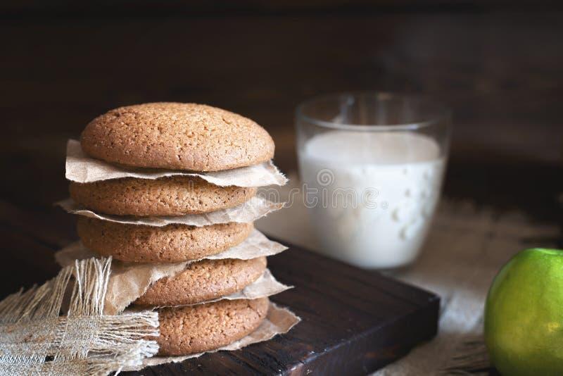 Selbst gemachte Hafermehlplätzchen des täglichen gesunden Frühstücks, Milch, Frucht auf dunklem Hintergrund lizenzfreies stockbild