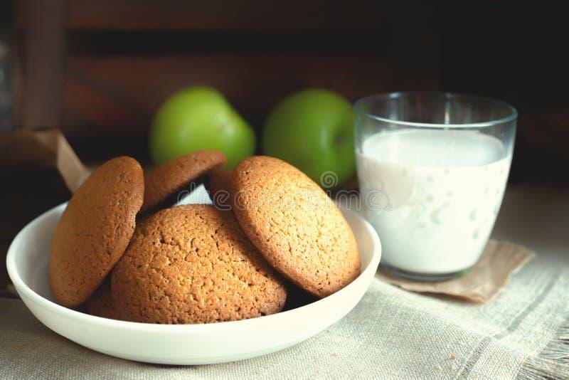 Selbst gemachte Hafermehlplätzchen des täglichen gesunden Frühstücks, Milch, Frucht auf dunklem Hintergrund stockfoto
