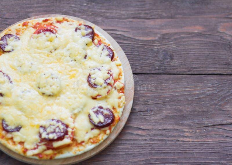 Selbst gemachte heiße Pizza mit Salami und Käse, Essiggurken und Tomaten auf dem hölzernen Hintergrund, essfertig stockfoto