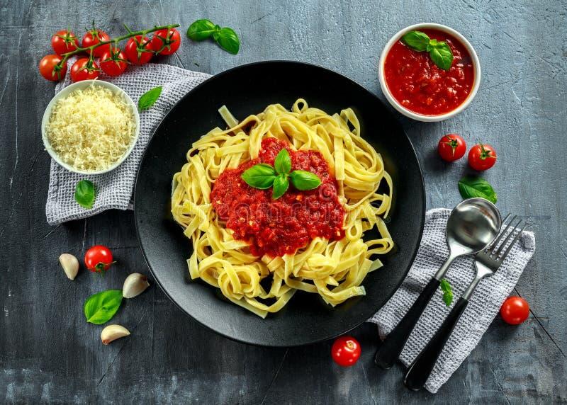 Selbst gemachte heiße Teigwaren mit Marinara-Soße, Basilikum, Knoblauch, Tomaten, Parmesankäseparmesankäse auf Platte lizenzfreies stockfoto