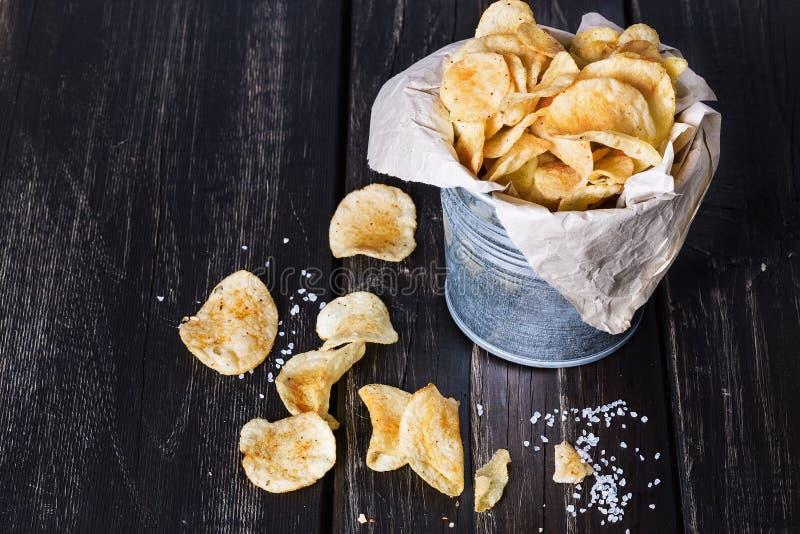 Selbst gemachte Kartoffelchips über dunklem hölzernem Hintergrund lizenzfreie stockfotos