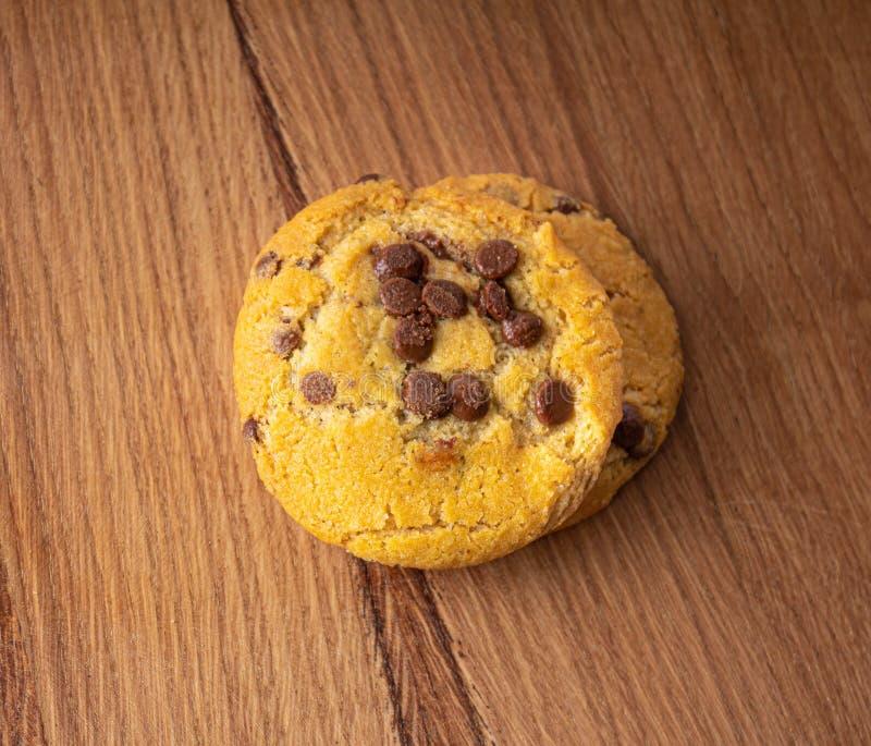 Selbst gemachte Kekse mit Schokoladenstücken auf einer hellen hölzernen Tabelle stockfotos