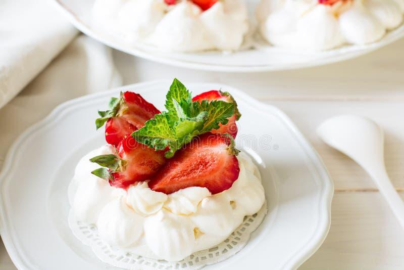 Selbst gemachte kleine Erdbeere-pavlova Meringe backt mit mascarpone Creme und frischen tadellosen Blättern zusammen stockbilder