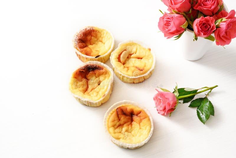 Selbst gemachte kleine Klumpenkuchen oder Muffins und rosa Rosen auf einer weißen Tabelle mit Kopienraum, Hintergrund verblaßt zu stockfoto