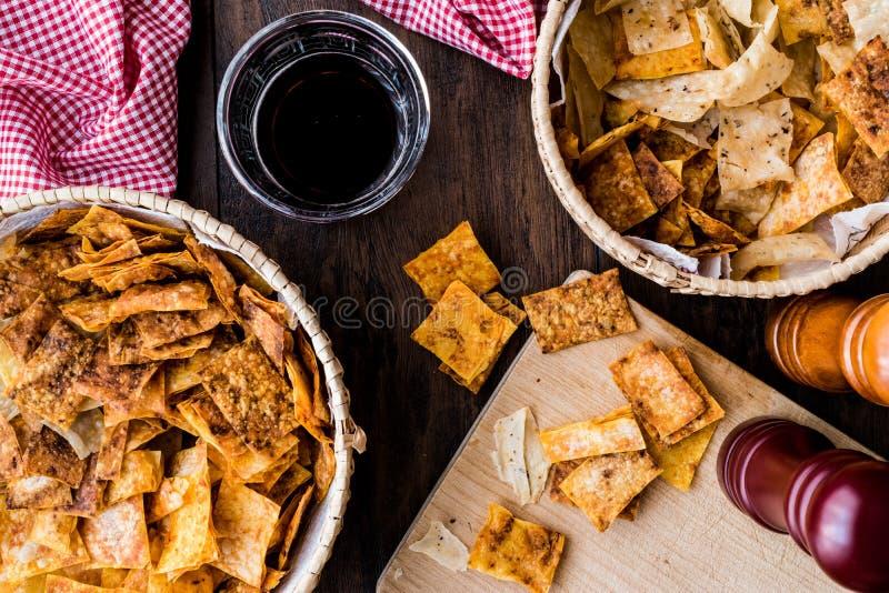 Selbst gemachte knusperige Chips/Snäcke in einer Weidenschüssel mit Getränk lizenzfreie stockfotos