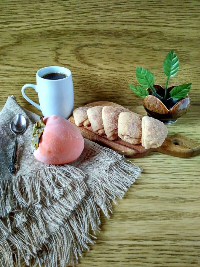 Selbst gemachte Kuchen mit Kaffee, Persimonen im Frost stockbild