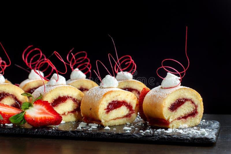 Selbst gemachte Kuchenrolle mit Erdbeercreme a auf einem schwarzen Schiefer stockbilder