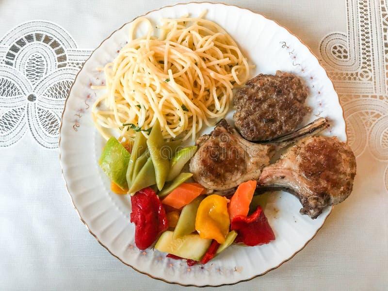 Selbst gemachte Lebensmittel-Platte mit Lamm-Hieb, Spaghettis und Gemüse lizenzfreie stockfotografie