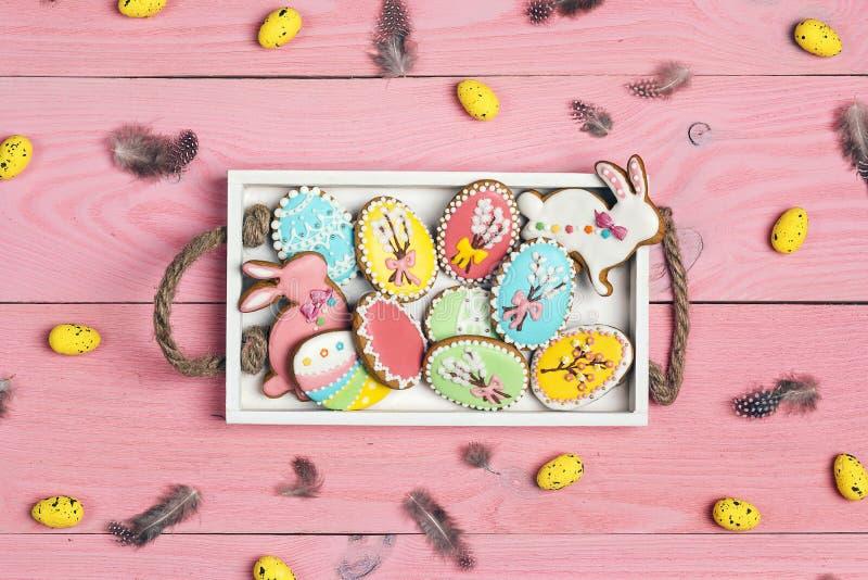 Selbst gemachte Lebkuchenplätzchen Ostern im Behälter auf einem rosa hölzernen Hintergrund lizenzfreies stockbild