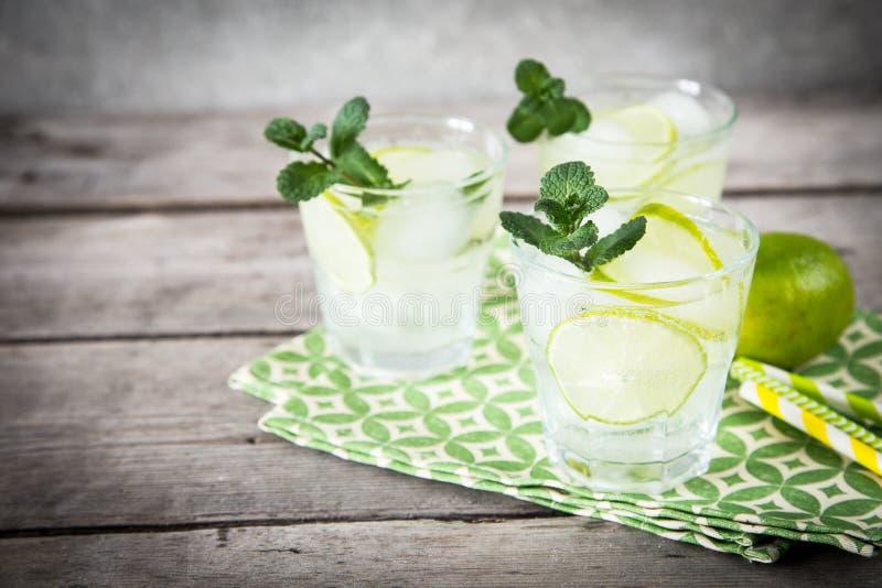 Selbst gemachte Limonade mit Kalk, Minze und Eis auf einem hölzernen Hintergrund lizenzfreie stockfotos