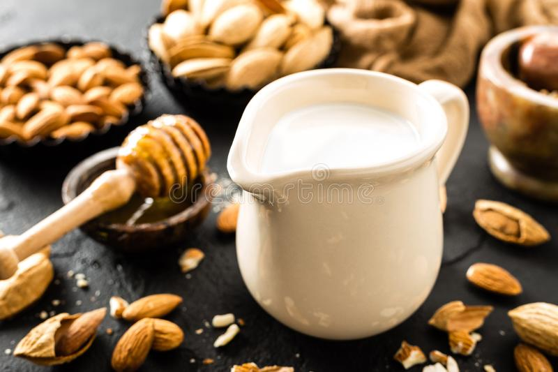 Selbst gemachte Mandelmilch im Krug Mandelmilch und -mandeln stockfotografie