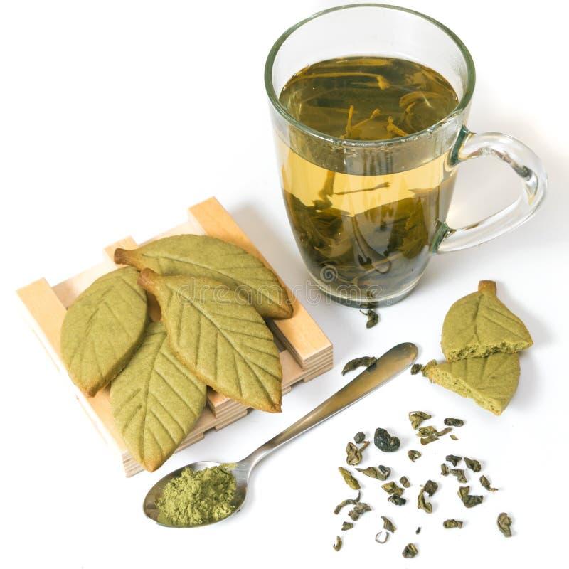 Selbst gemachte matcha Keksplätzchen grünen Tees in Form von grünen Teeblättern auf dem hölzernen Stand nahe der Schale des grüne lizenzfreie stockfotografie