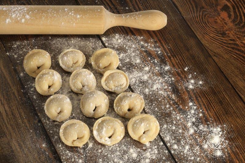 Selbst gemachte Mehlklöße und Nudelholz des rohen Fleisches Hölzerne Tabelle lizenzfreie stockfotos