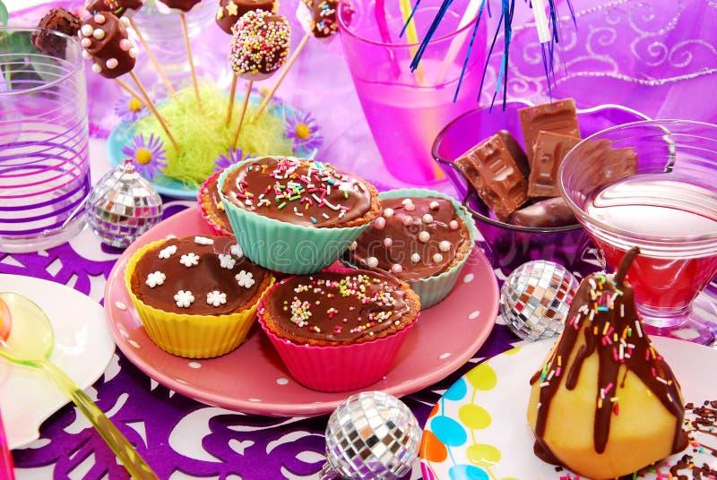 Selbst gemachte Muffins auf Geburtstagsfeiertabelle lizenzfreie stockbilder