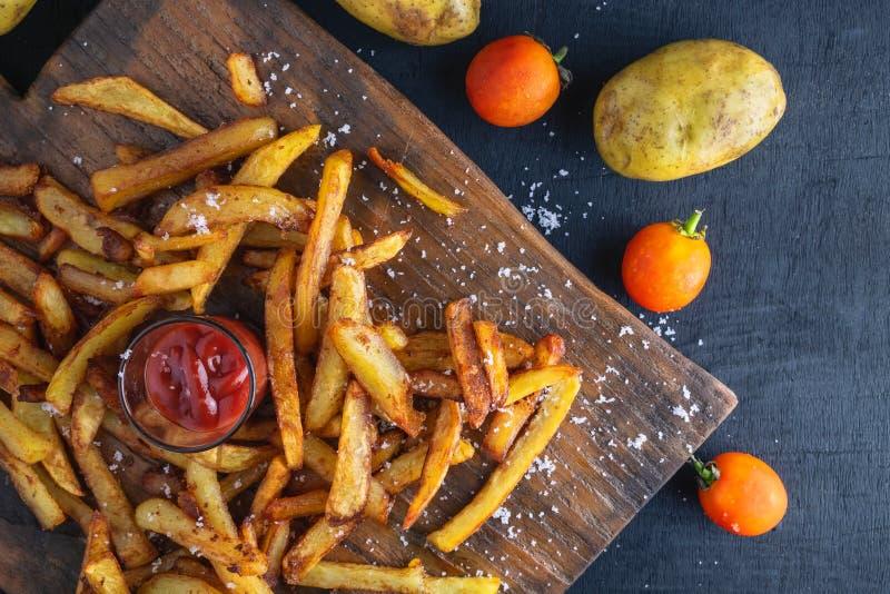 Selbst gemachte Ofenkartoffel brät mit Ketschup auf hölzernem hinterem Boden lizenzfreies stockfoto
