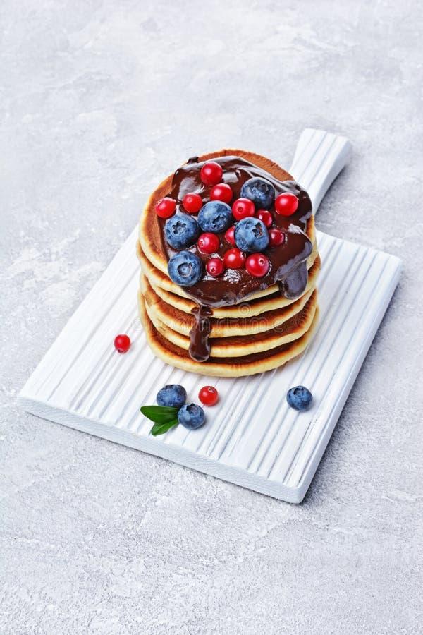 Selbst gemachte Pfannkuchen des geschmackvollen Frühstücks mit frischer Blaubeer-, Moosbeer- und Schokoladencreme auf weißem hölz stockfotos