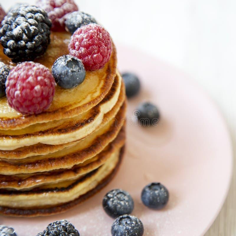 Selbst gemachte Pfannkuchen mit Beeren auf einer rosa Platte, Seitenansicht Gesunde Sommerfrühstück Nahaufnahme stockfotografie