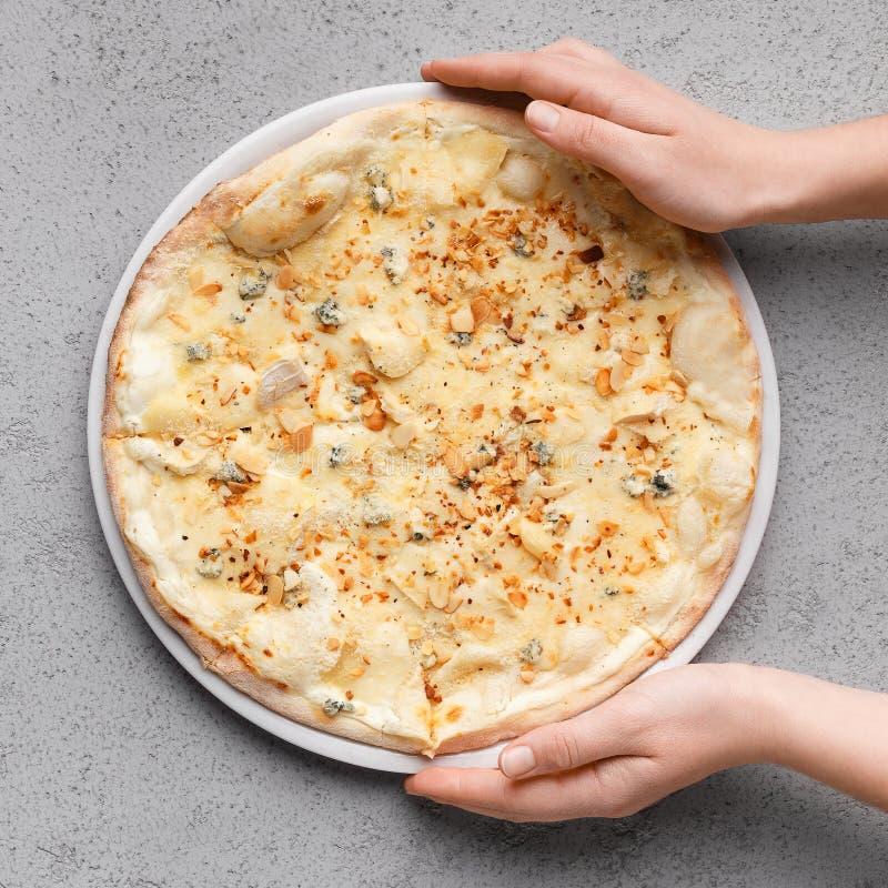 Selbst gemachte Pizza Frau, die k?sige Pizza auf Tabelle setzt stockfoto