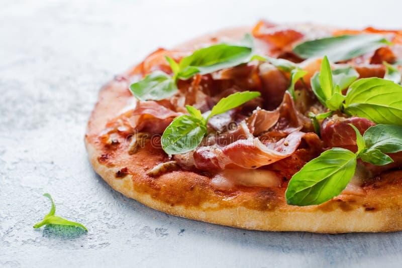 Selbst gemachte Pizza mit jamon, Mozzarella und frischen Basilikumblättern auf einem alten Hintergrund des Leichtbetons stockfoto