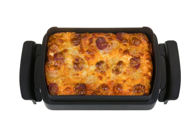 Selbst gemachte Pizza mit Salami, Speck, Tomatensauce, gelber Käse, Mozzarella in einer Teflonbackform lokalisiert auf weißem Hin lizenzfreie stockfotografie