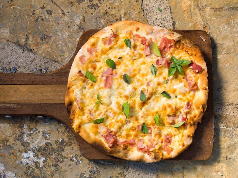 Selbst gemachte Pizza mit Schinken auf einer hölzernen Schaufel stockfotografie
