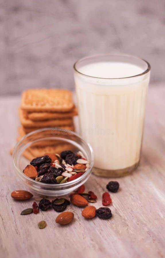 Selbst gemachte Plätzchen und ein Glas Milch und Samen: Nüsse, Mandeln, Oblaten, Rosinen Gesundheitskekse mit Milch auf rustikale stockfoto