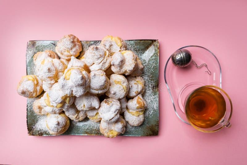 Selbst gemachte profiteroles dienten auf einer Platte mit einer Tasse Tee auf einem rosa Hintergrund Flache Lage stockfoto