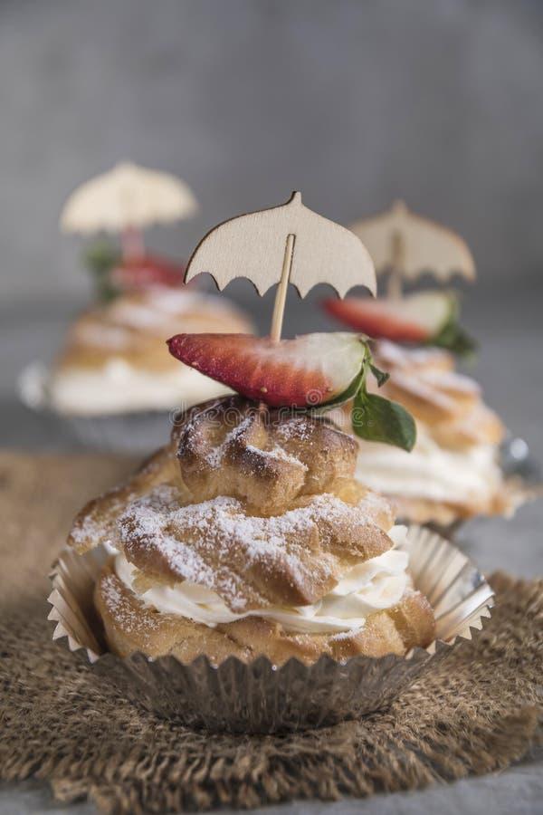Selbst gemachte profiteroles mit Sahne, Erdbeeren und Minze Nachtisch f?r Feinschmecker lizenzfreies stockbild