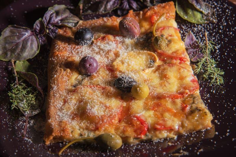 Selbst gemachte rechteckige Pizza auf der dunklen Platte mit Oliven und Parmesankäseparmesankäse und -kräuter stockbilder