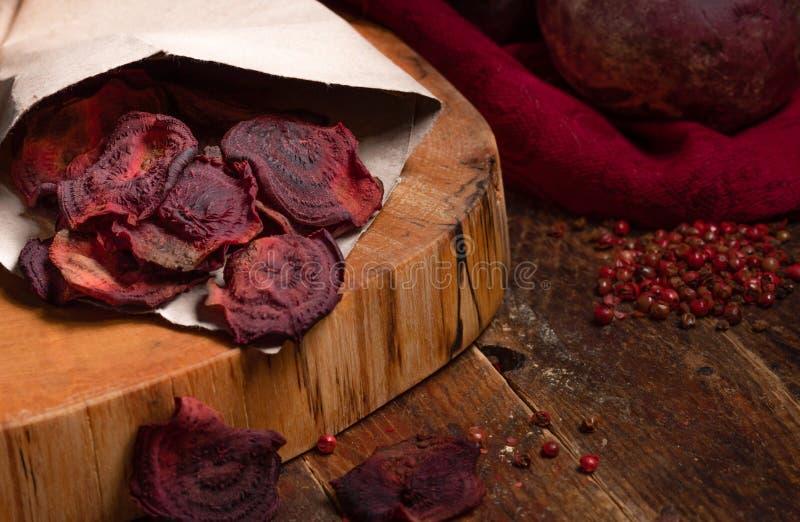 Selbst gemachte Rote-Bete-Wurzeln Chips in der Papiertüte auf Schnitt auf Holztisch stockbilder