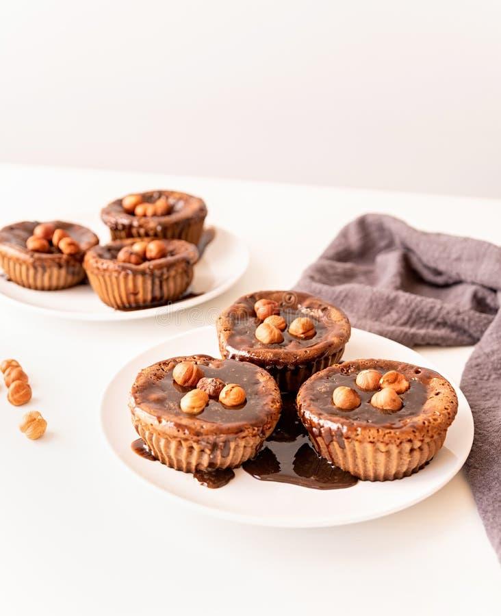 Selbst gemachte Schokoladenmuffins mit Belag und Walnüssen auf weißer Tabelle stockfotos