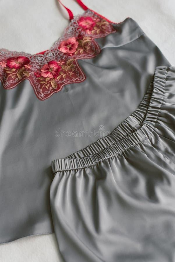 selbst gemachte Seidenpyjamas, die auf dem Bett ohne jedermann liegen graue Pyjamas mit roter Spitze auf einem beige Hintergrund lizenzfreie stockfotografie