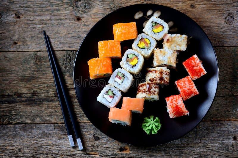 Selbst gemachte Sushi mit Lachsen, tobiko Kaviar, Omelett, Gurke, indischem Sesam und Weichkäse auf altem hölzernem Hintergrund R lizenzfreie stockfotos