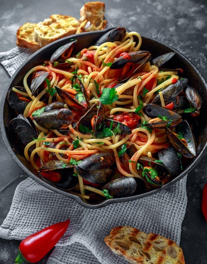 Selbst gemachte Teigwaren-Spaghettis mit Miesmuscheln, Tomatensauce, Paprikas und Petersilie in der rustikalen Bratpfanne, Wanne  stockfotografie